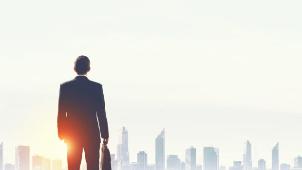 40473699 - rear view of businessman looking at sunset above city