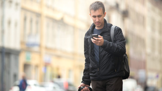 42259356 - young smiling attractive man with luggage bag walking in the rainy city street looking at smartphone, using app, gps, searching for direction, texting, making call, travelling, wearing casual clothes